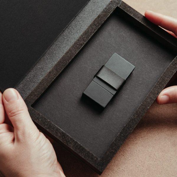 Caja para entregar USB fabricada con piel vegana de color negro y madera. Cajas para pendrive USB.
